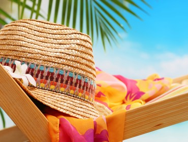 Summer holiday setting with straw hat on beach chair